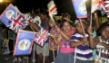 Children waving flags to greet Prince Harry (Photo 1 of 5 photo(s)).