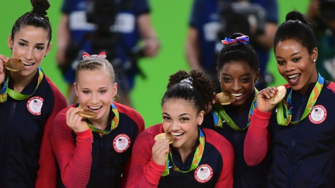 US gymnasts Alexandra Raisman, Madison Kocian, Lauren Hernandez, Simone Biles and Gabrielle Douglas celebrate with their gold medals on the podium during the women's team final Artistic Gymnastics at the Olympic Arena during the Rio 2016 Olympic Games in Rio de Janeiro on August 9, 2016. / AFP / Emmanuel DUNAND        (Photo credit should read EMMANUEL DUNAND/AFP/Getty Images)